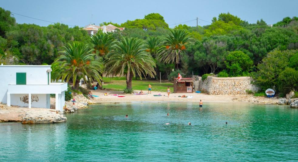 Der Blick auf die Cala Blanca zeigt ein weiteres Gesicht der Calas auf Menorca. Es ist das Bild, das man von den mediterranen Stränden in sich trägt: weite und ausgedehnte Sandstrände, von Palmen gesäumt, einladende Liegestühle - Urlaubsstimmung eben. Wenn wir unser Glückshotel Menorca buchen, haben wir bei der Wahl des Strandes alle Freiheiten und können uns für eine verwunschene und abgeschiedene Cala entscheiden oder für eine große und offene wie eben hier die Cala Blanca. It's up to you! (#1)